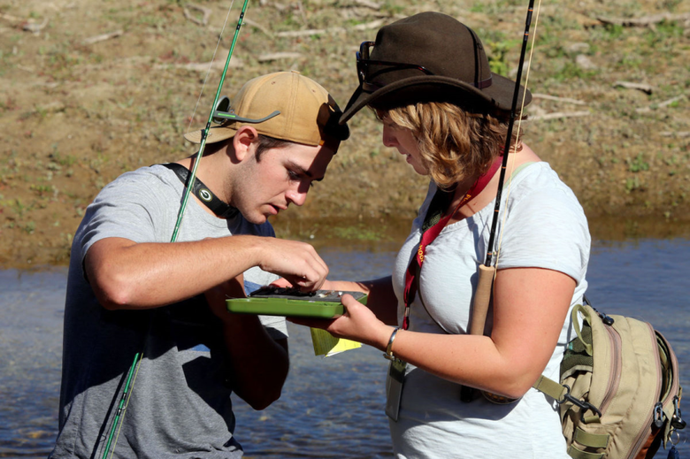 Two young adults fly fishing
