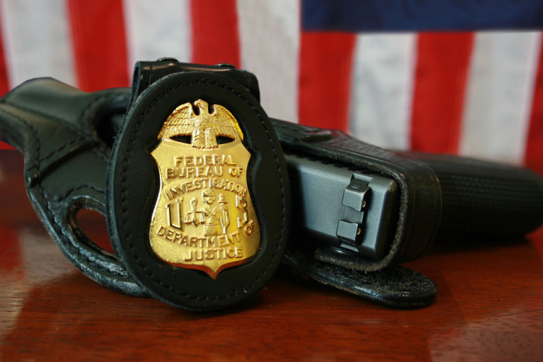 FBI Badge and Gun in front of a US flag