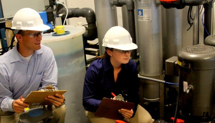 Two employees with white hardhats in a manufacturing company