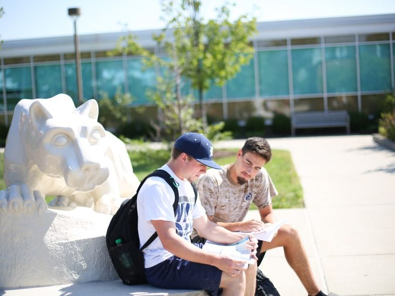 two students sitting at the lion shrine reading