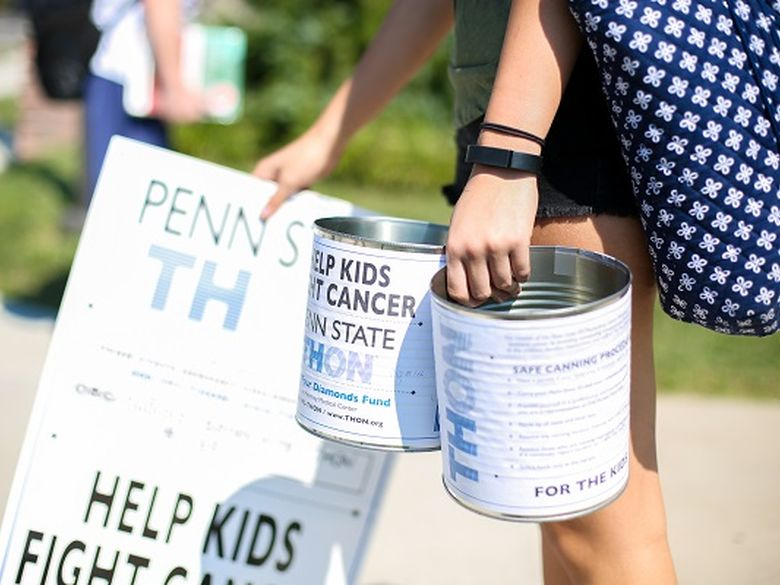 students holding dance marathon cans