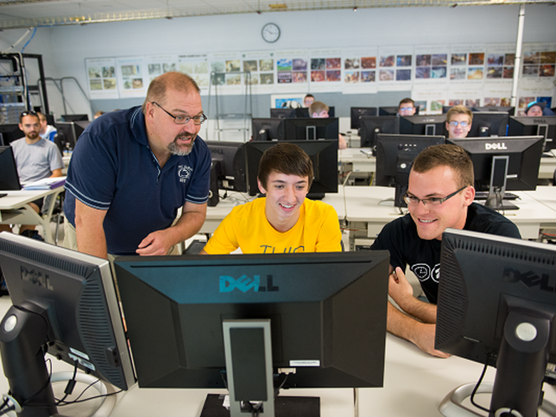 IST students working with instructor in technology class